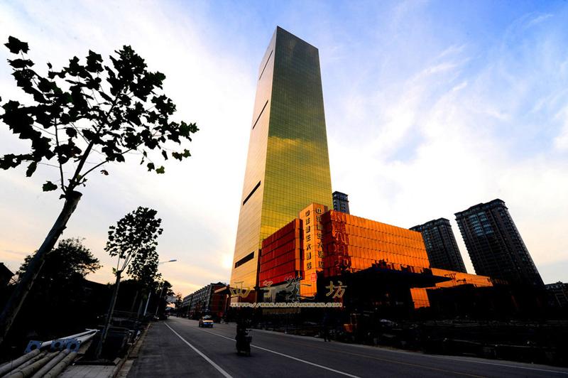 """2013年10月18日,江苏南通市海安县,位于苏中地区的一座县城,近来随着一栋被网友誉为""""大金砖""""的建筑—中洋豪生大酒店揭开神秘的面纱,引发广泛关注。这座由江苏中洋集团江苏中洲置业有限公司投资建设的白金五星级酒店,定位是中国最富特色的酒店。图为整座酒店全部采用象征高贵的""""黄""""色设计、建造。在当地百姓口中,更习惯称这座高200米,通体金黄的建筑为""""大金条""""。定位为白金五星级的中洋豪生大酒店总投资超过15亿元,总面积12万"""