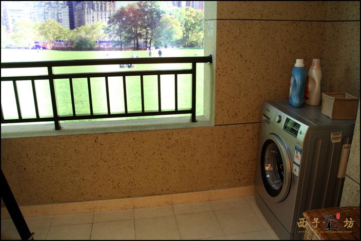 客厅带有阳台,这里放上了洗衣机等家用物品图片